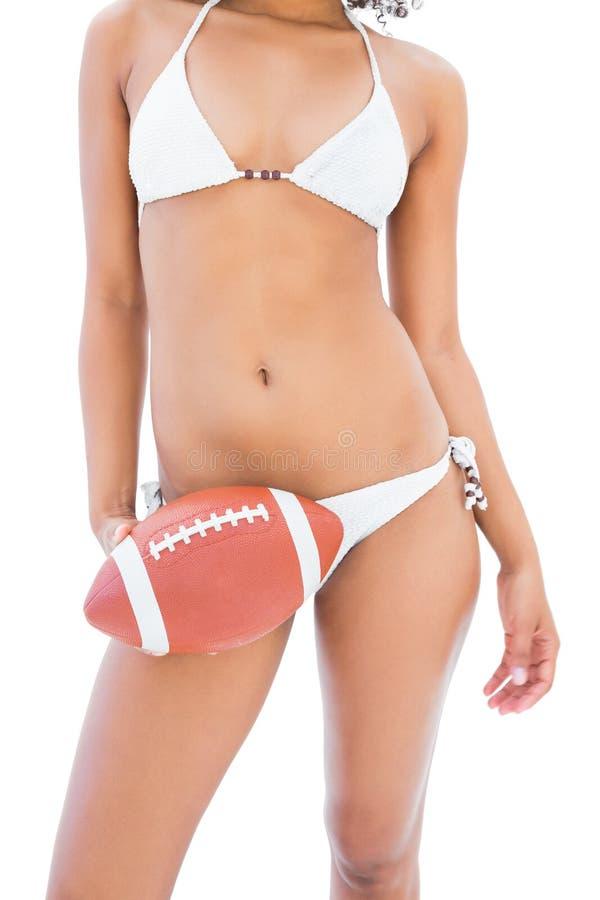 Geeignetes Mädchen im weißen Bikini, der amerikanischen Fußball hält lizenzfreies stockbild