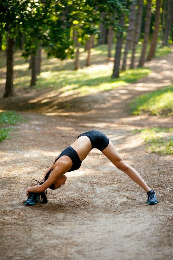 Geeignetes, muskulöses Mädchen in der Sportkleidung, die Übungen mit ihren Beinen ausdehnend seitlich, auf grünem Parkhintergrund stockbilder