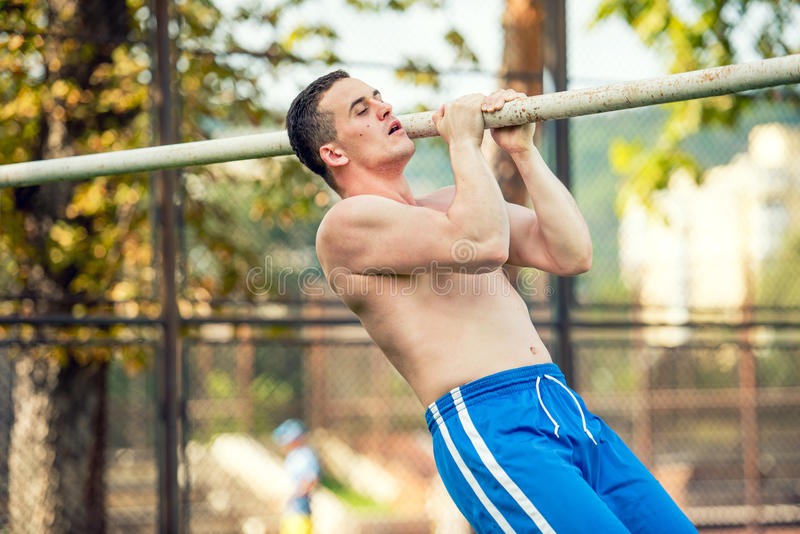 Geeignetes Trainingskonzept des Kreuzes mit muskulösem Eignungsspieler und persönlichen dem Trainer, die im Park ausarbeitet lizenzfreies stockbild