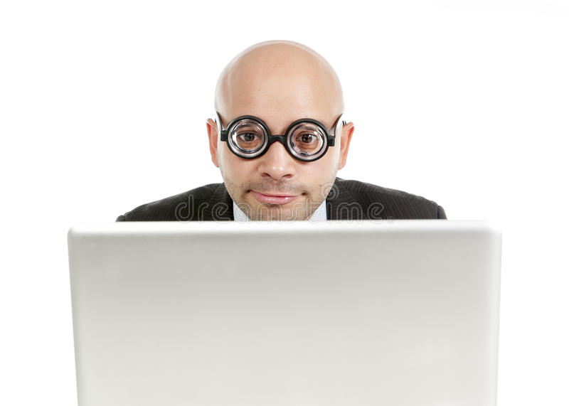Geek and freak bald head businessman with computer laptop wearing thick glasses looking nerd royalty free stock image