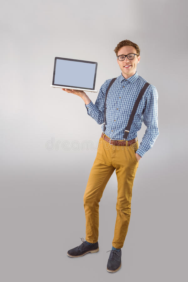 Geeky businessman showing his laptop. On grey background stock images