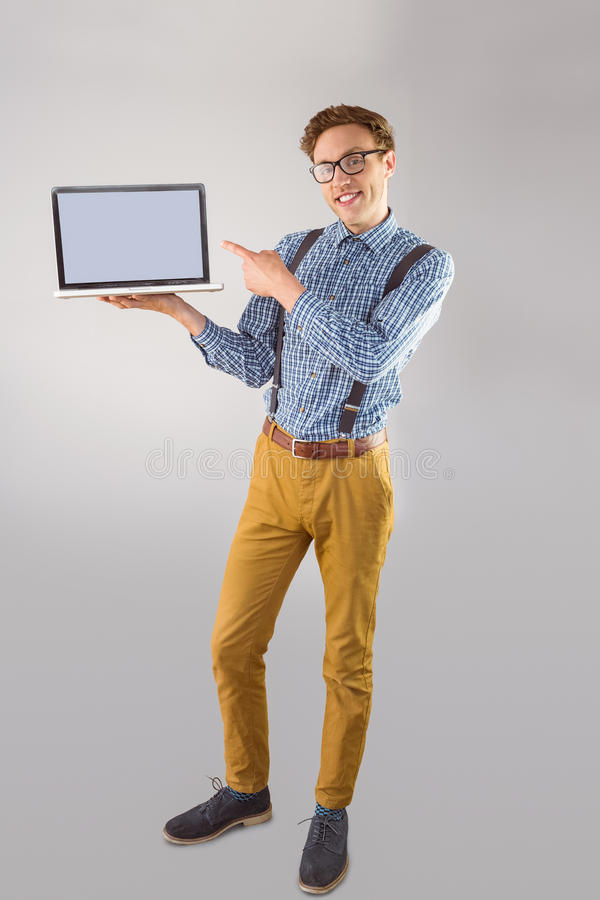 Geeky businessman showing his laptop. On grey background royalty free stock photo