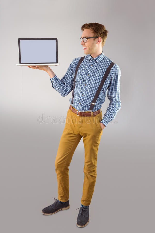 Geeky businessman showing his laptop. On grey background stock image