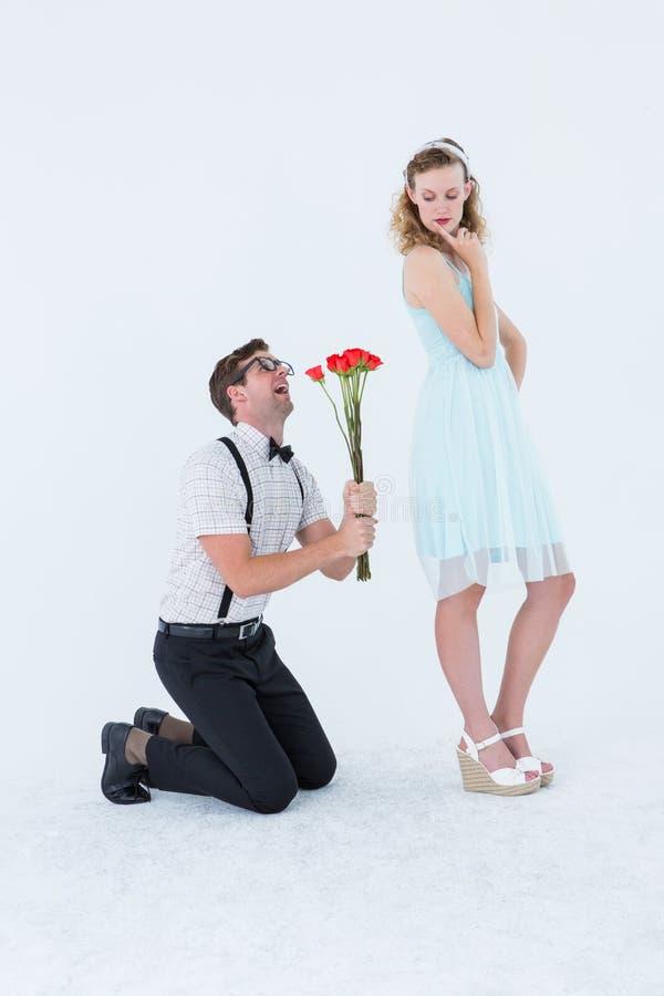 Geeky die hipster zijn meisje bedelen die rozen nemen stock fotografie