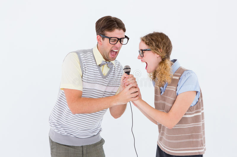 Geeky hipster couple singing into a microphone. On white background stock photography