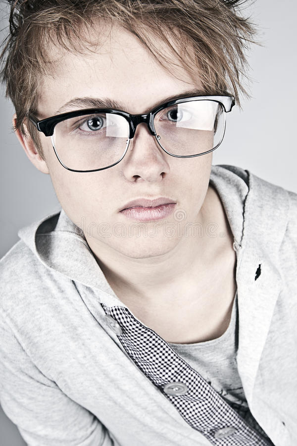 Geeky Looking Teenager against Grey Background stock images