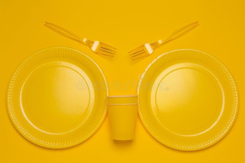Geel beschikbaar vaatwerk op een gele achtergrond stock foto
