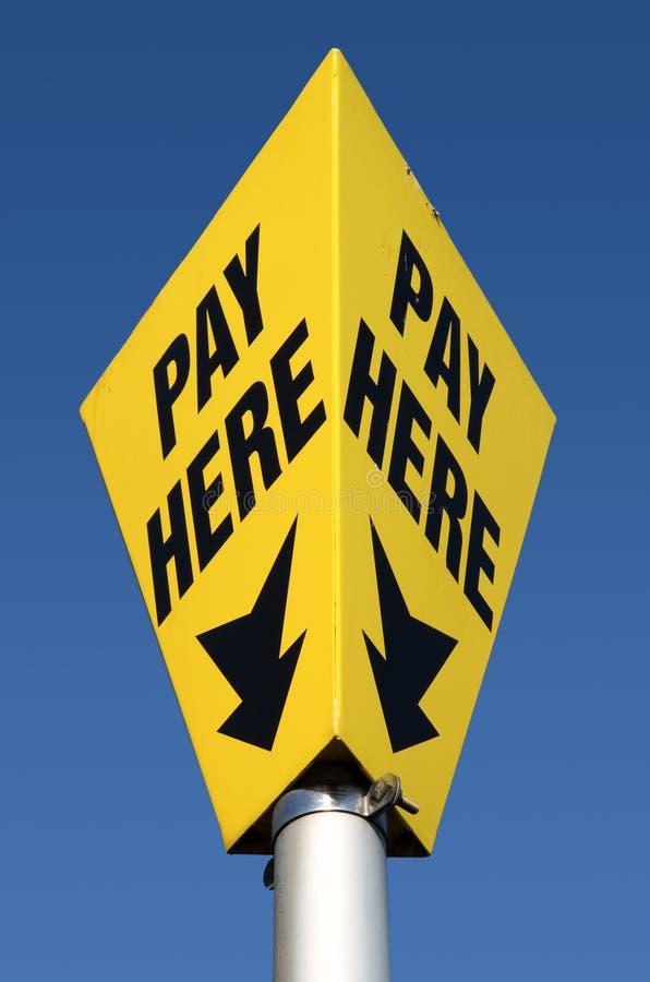 Geel betaal hier het teken van het autoparkeren. stock foto's