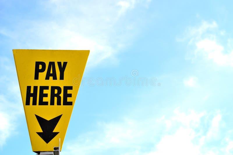 Geel betaal hier parkeerterreinteken stock afbeelding