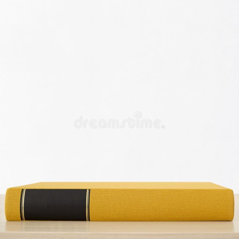 Geel boek met zwart kader op stekel op de lijst stock afbeelding