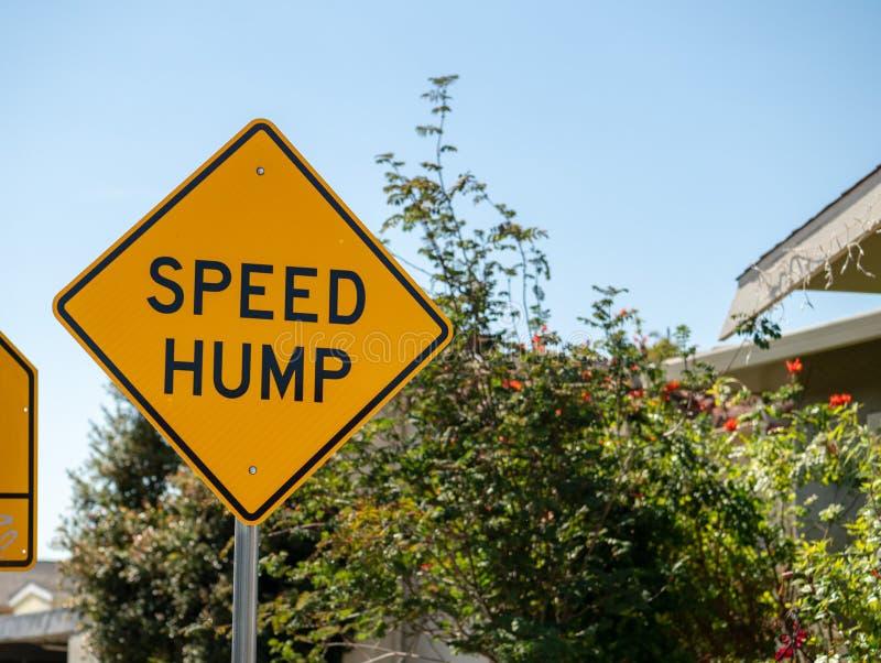 Geel de straatteken van de snelheidsbult in een lokale buurtstraat royalty-vrije stock foto's