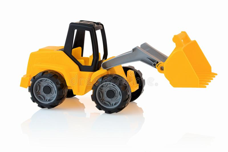 Geel die graafwerktuig op witte achtergrond met schaduwbezinning wordt geïsoleerd Plastic kindstuk speelgoed op witte achtergrond royalty-vrije stock afbeeldingen
