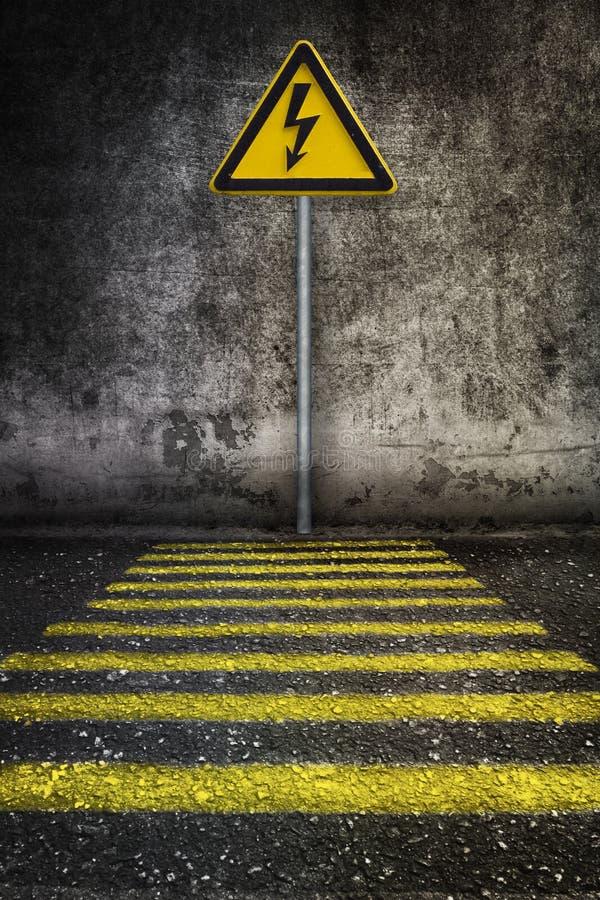 Geel elektriciteitswaarschuwingsbord bij grungemuur voor voetgangersoversteekplaats royalty-vrije stock foto's