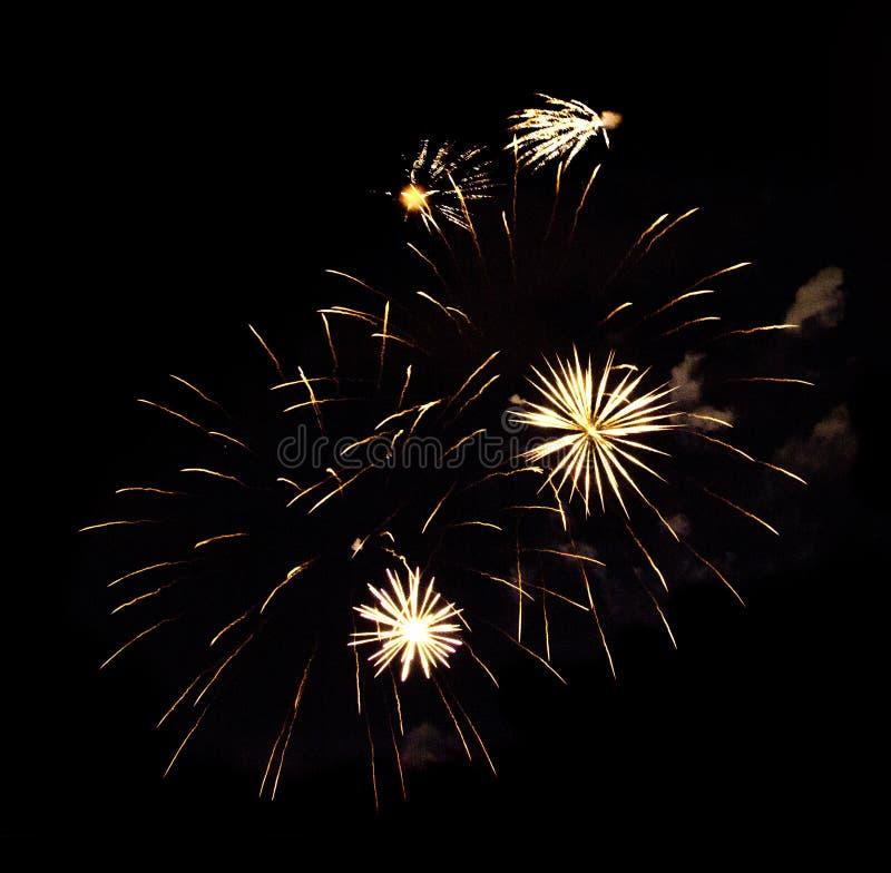Geel en wit die vuurwerk op zwarte achtergrond wordt geïsoleerd stock foto's