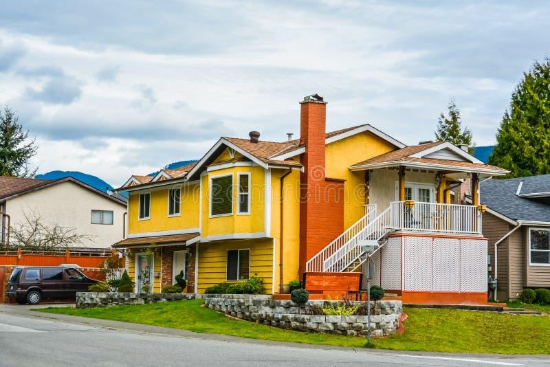 Geel familiehuis met een auto op de oprijlaan op bewolkte hemelachtergrond royalty-vrije stock afbeelding