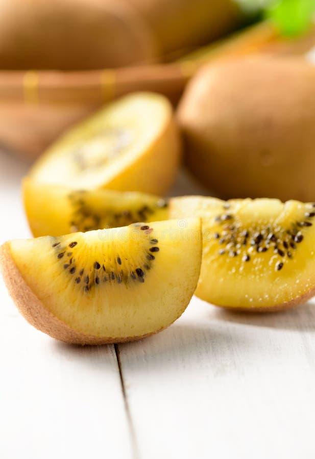 Geel gesneden kiwifruit op wit hout royalty-vrije stock foto's