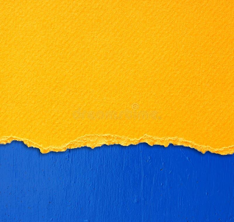 Geel geweven gescheurd document over blauwe muurachtergrond royalty-vrije stock foto