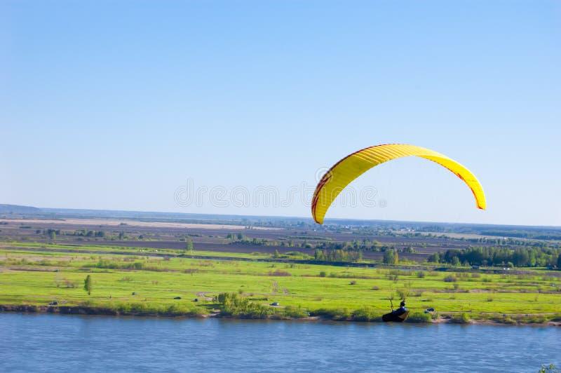 Geel Glijscherm in blauwe hemel boven de rivier en de rivieroever Het panorama van het vogel` s oog Tom River De stad van Tomsk,  royalty-vrije stock afbeeldingen