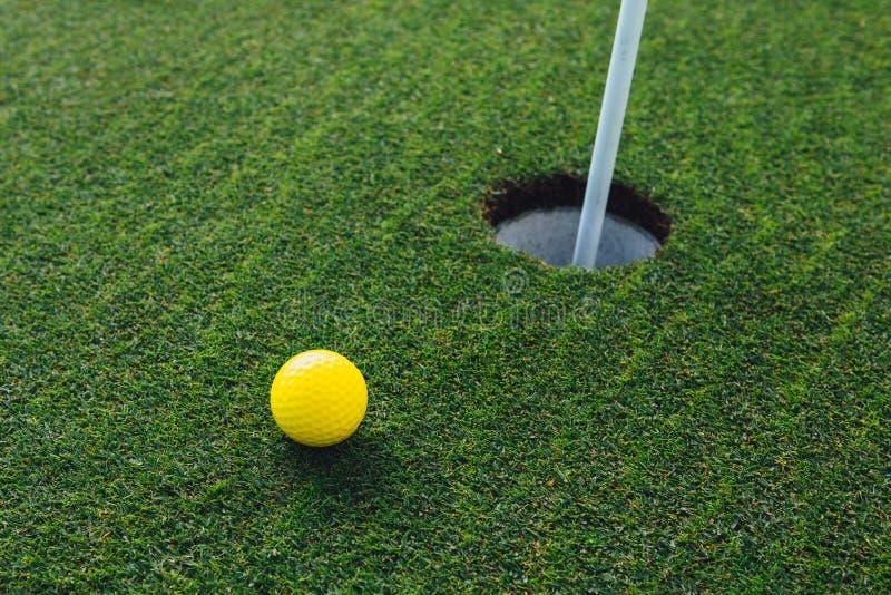 Geel golfbal nabijgelegen gat met speldvlag, groene grasachtergrond royalty-vrije stock afbeeldingen