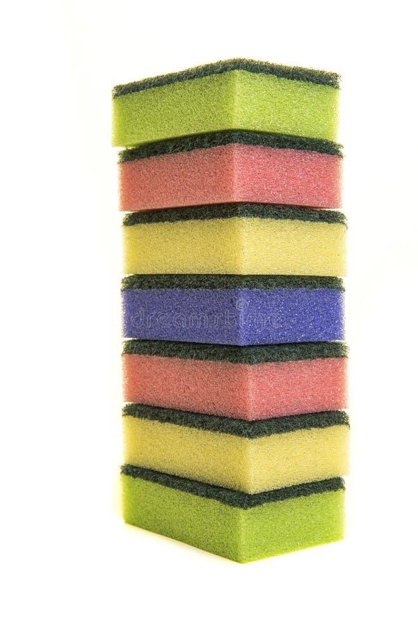 Geel, groen, roze en purper sponsenschuursponsje op een stapelisola stock foto