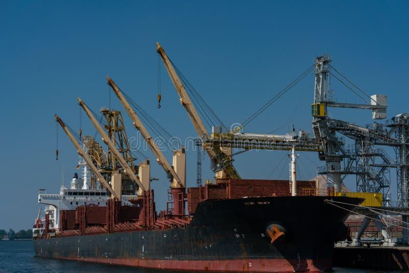 Geel havenkranen en schip bij de industriële haven in Rostock stock fotografie