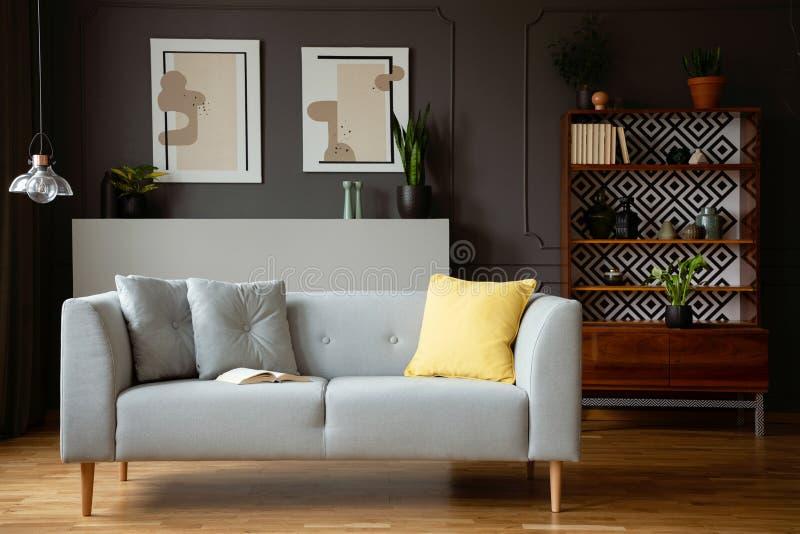 Geel hoofdkussen op grijze laag in uitstekend woonkamerbinnenland met lamp en affiches Echte foto stock fotografie