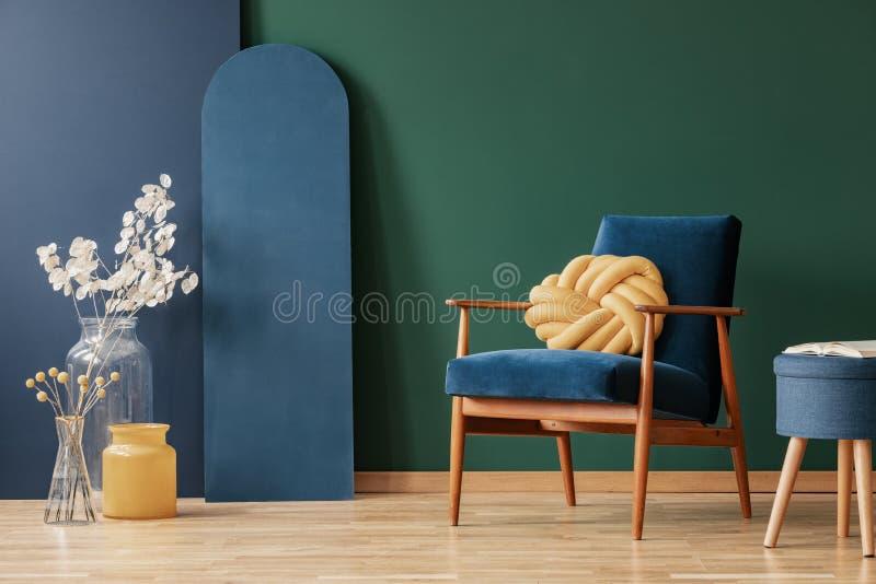 Geel hoofdkussen op houten leunstoel in blauw en groen vlak binnenland met bloemen en kruk Echte foto royalty-vrije stock foto's