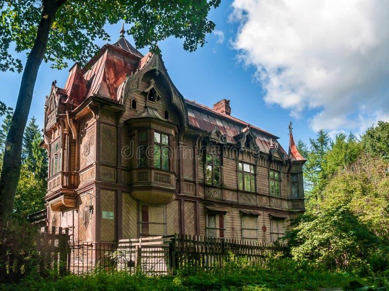 Geel houten two-storey huis in eclectische stijl met erker stock afbeeldingen