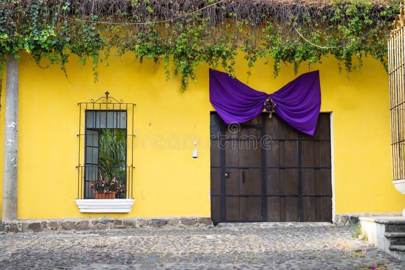 Geel huis met houten haven en purper lint, Antigua, Guatemala stock foto