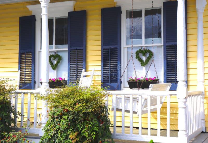 Geel Huis, Portiekschommeling, en Bloemen stock fotografie