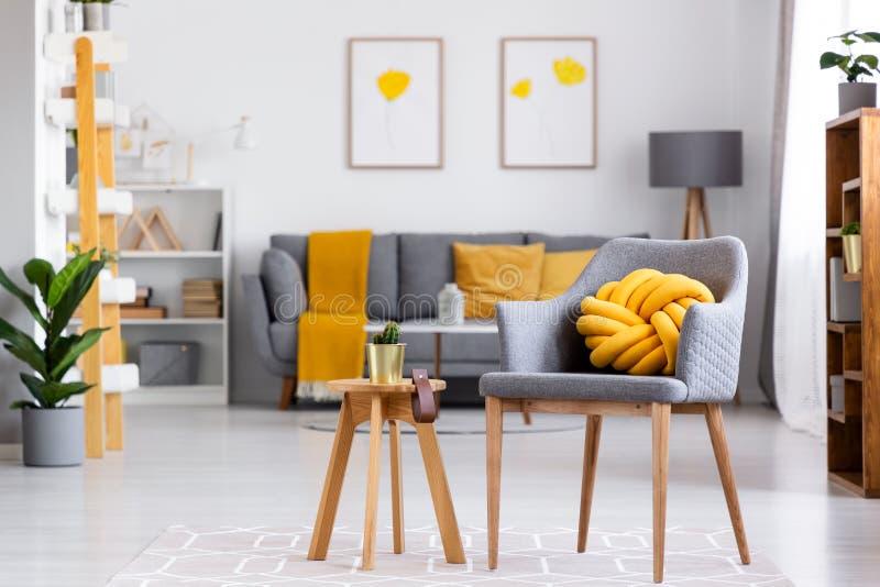 Geel knoopkussen op een grijze leunstoel die zich naast houten bevinden stock afbeeldingen