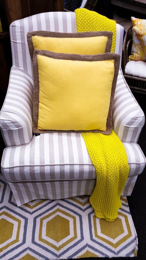 Geel kussen op stoel in mengeling van kleuren binnenlandse ontwerper stock afbeelding
