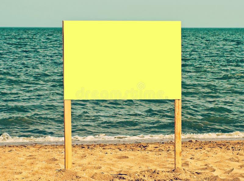 Geel leeg aanplakbord op zandig strand Voeg enkel uw tekst toe stock foto's