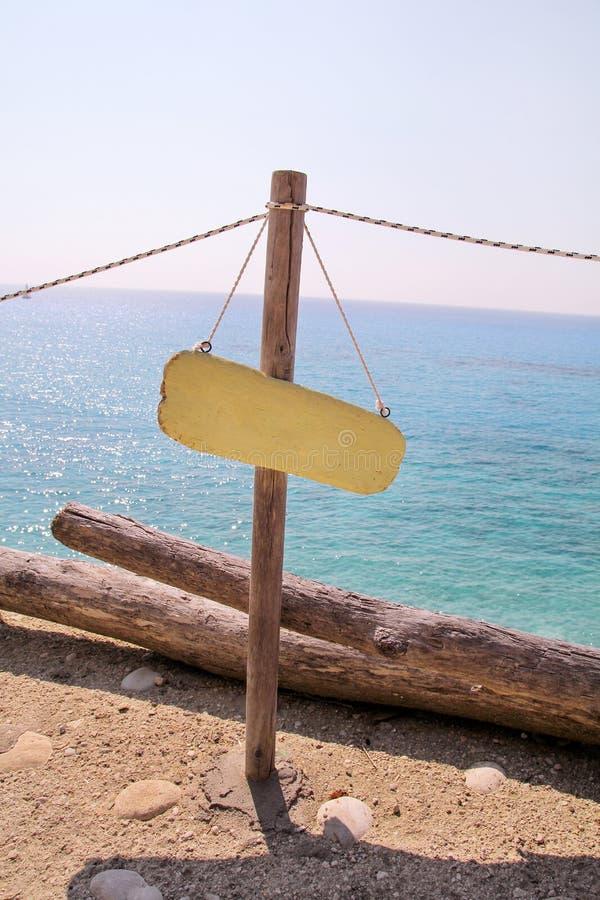 Geel leeg aanplakbord op zandig strand Voeg enkel uw tekst toe Strandteken door overzees Leeg rustiek houten teken op strand stock foto's