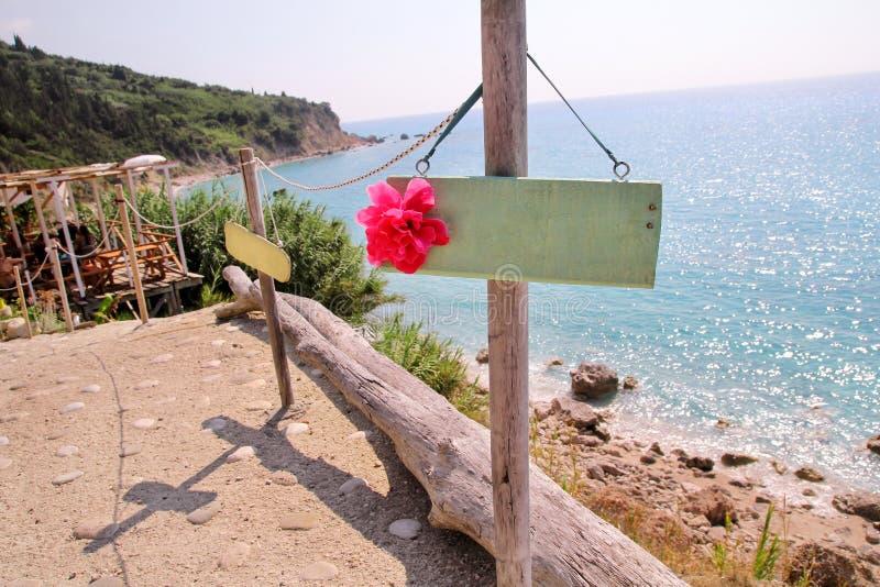 Geel leeg aanplakbord op zandig strand Voeg enkel uw tekst toe Strandteken door overzees Leeg rustiek houten teken op strand stock afbeelding