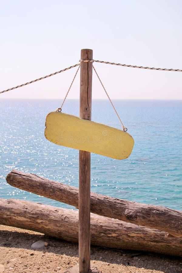 Geel leeg aanplakbord op zandig strand Voeg enkel uw tekst toe Strandteken door overzees Leeg rustiek houten teken op strand stock foto