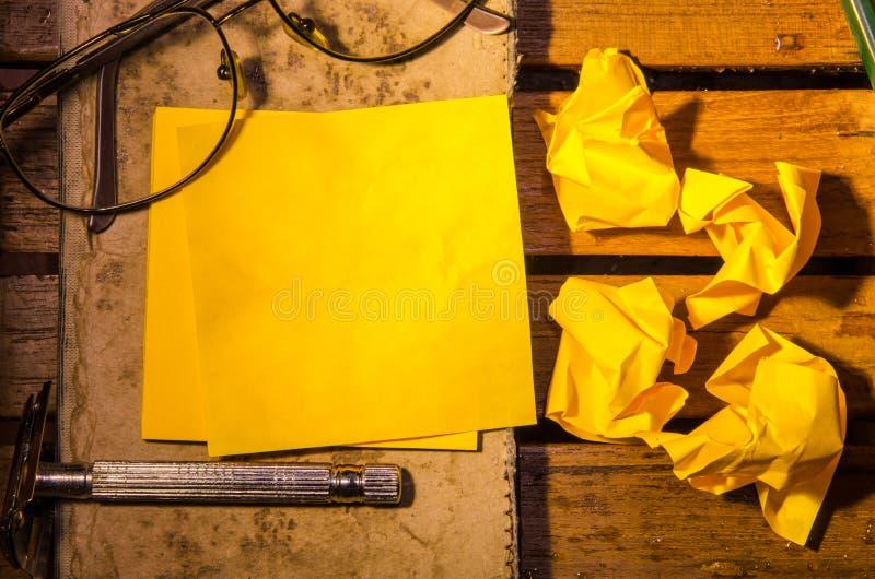 Geel leeg document met verfrommeld document met glazen met potlood op een oud boek royalty-vrije stock afbeelding