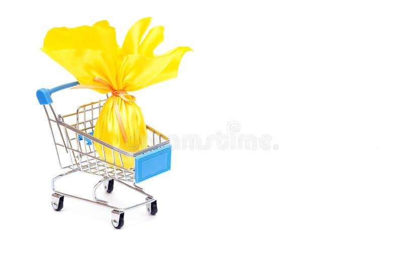 Geel paasei in een het winkelen karretje op een witte achtergrond, het concept het winkelen en giften voor de vakantie Pasen royalty-vrije stock foto