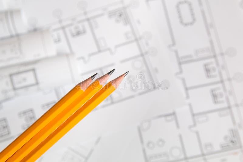 Geel potlood op architecturale blauwdrukachtergrond stock afbeeldingen