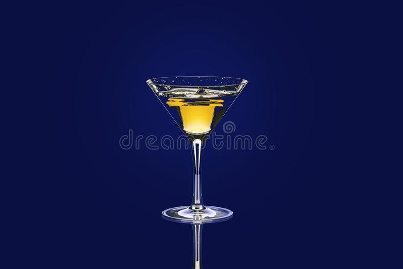 Geel-rode cocktail in Baikal voor martini met een mooie plons tegen dalingen op een blauwe achtergrond stock fotografie