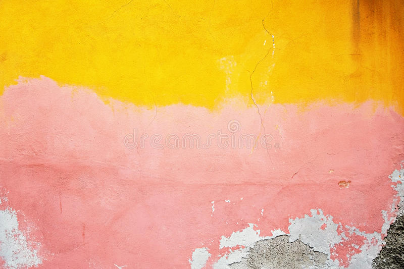 Geel, roze, grijs vernietigd pleister bij een bakstenen muur Grunge cem stock afbeeldingen