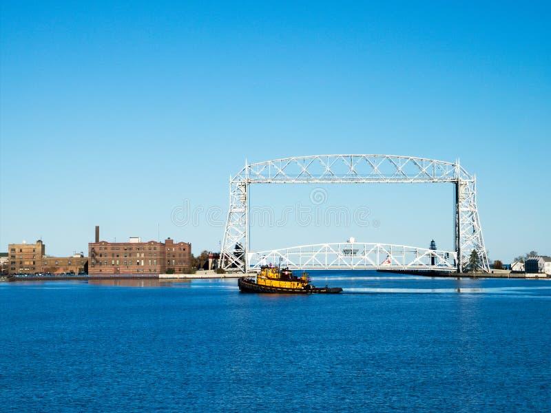 Geel Tug Boat vaart dichtbij lucht de liftbrug van Duluth Minnesota in recente middag stock fotografie