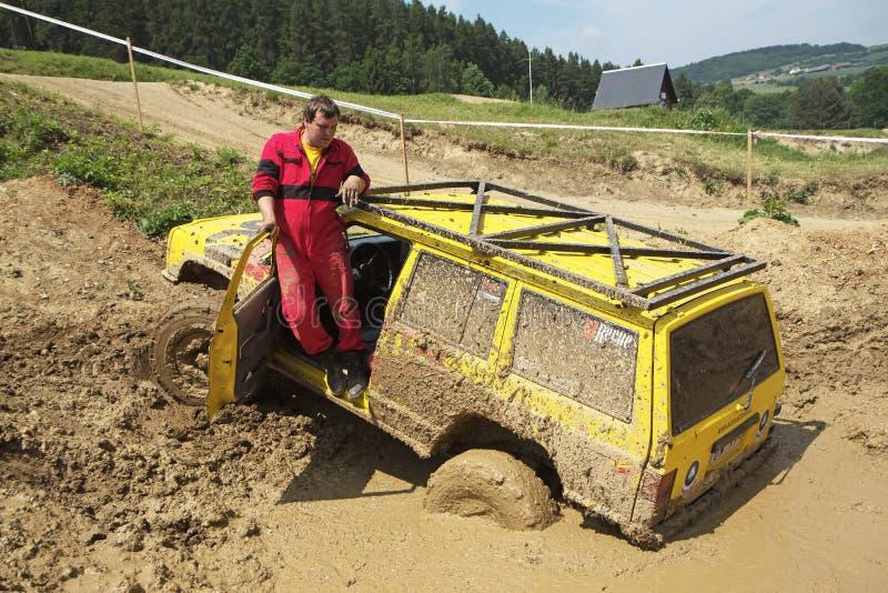 Geel van wegauto in modderig terrein is verdronken dat stock afbeelding