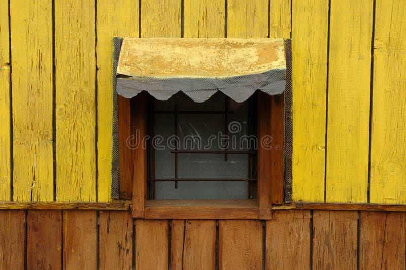 Geel venster van een houten plattelandshuisje stock fotografie