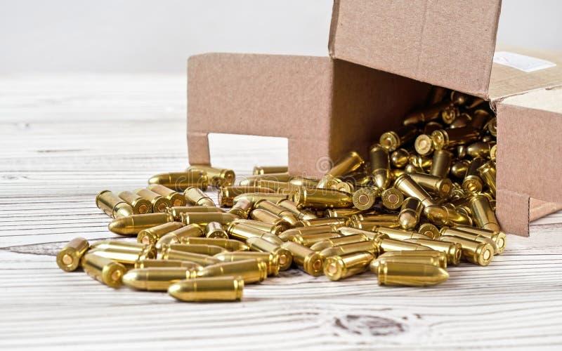 Geel vuurwapen gemorst uit kartonnen kartonnen doosje op de witte borden - dicht stock foto