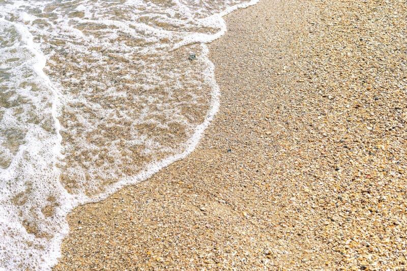 geel zand en witte plons van water in overzees stock foto