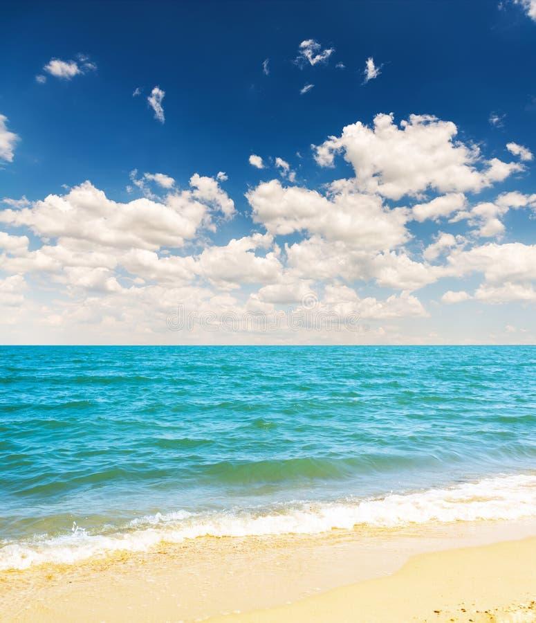 geel zandstrand en blauwe overzees met wolken in hemel royalty-vrije stock afbeeldingen