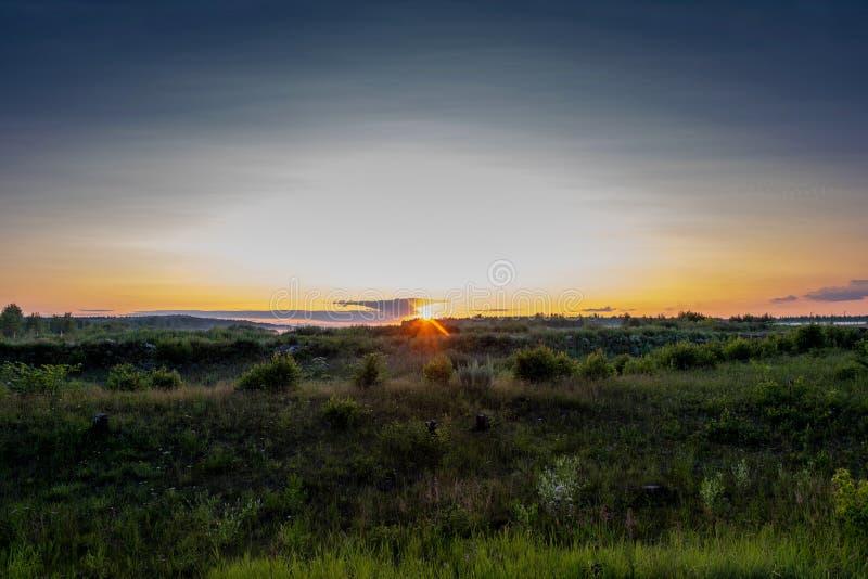 Geeloranje schijf van de het plaatsen zon over de horizon en een weinig bewolkt stock afbeelding