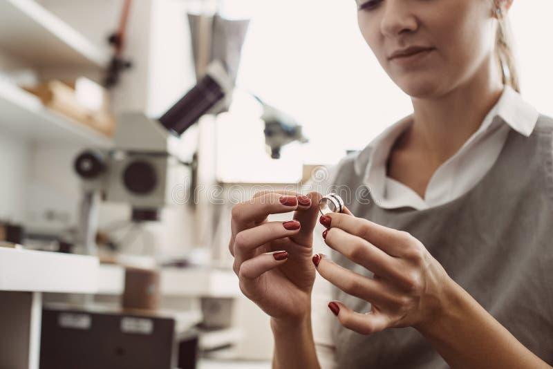 Geen grens aan perfectie Sluit omhoog van vrouwelijke juwelier onderzoekend de zilveren ring op workshop stock foto