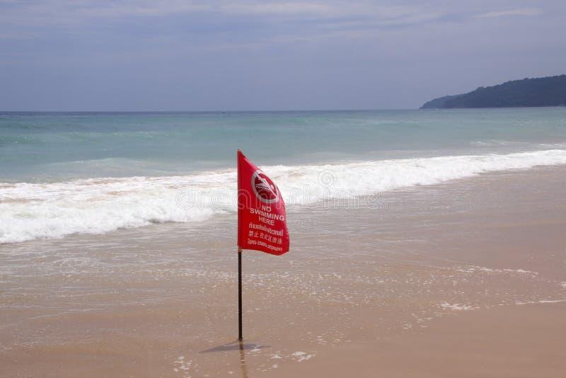 Geen hier het Zwemmen van rode vlag op een strand in Phuket, Thailand De waarschuwingsinschrijving is in de Engelse, Thaise en Ru royalty-vrije stock afbeeldingen